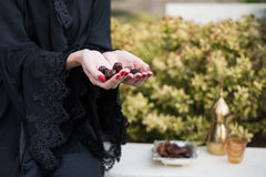 Middle Eastern Woman Offering Dates. Middle Eastern woman holding date fruits in hands Stock Photos