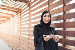 Middle Eastern Woman Offering Dates. Middle Eastern woman in traditional abaya offering date fruits Stock Image
