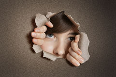 Middle eastern woman peeking from ripped white paper hole Stock Photos