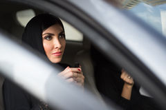 Middle Eastern Woman Sitting Inside a Car. Beautiful Middle Eastern Woman Sitting inside a Car, Preparing to Apply Make-up Royalty Free Stock Photography