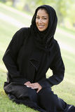 A Middle Eastern woman sitting in a park Stock Photos