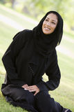 A Middle Eastern woman sitting in a park Royalty Free Stock Image