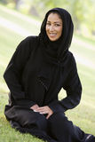 A Middle Eastern woman sitting in a park Stock Photo
