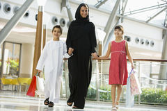 A Middle Eastern woman with two children shopping. A Middle Eastern woman with two children in a shopping mall royalty free stock photos