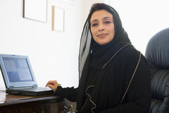 A Middle Eastern woman using computer. A Middle Eastern woman sitting in front of a computer at home Stock Photography