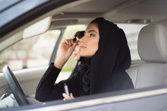 Middle Eastern Women Sitting Inside a Car and Applying Make-up Stock Photography
