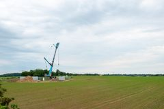 A wind turbine is erected with the help of a large crane royalty free stock photo