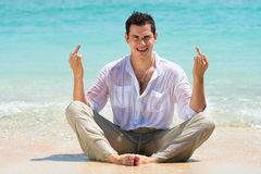 Middle finger gesture by man on a beach Stock Images