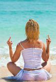 Middle finger gesture by woman on a beach Royalty Free Stock Image
