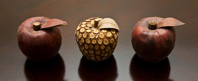 Middle Fruit. A wooden pineapple sits in the middle of two red apples royalty free stock image