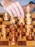Middle game - the hand with knight makes a move on chess Board Royalty Free Stock Photo