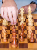 Middle game - the hand with pawn makes a move on chess Board Stock Photos