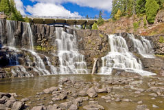 Middle gooseberry falls. Boulder strewn middle gooseberry falls and minnesota highway 61 bridge Royalty Free Stock Images