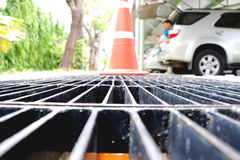 Middle point focus of steel drain water flows down through the steel manhole cover on a sunlight afternoon. Royalty Free Stock Photography