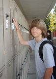 Middle schooler at locker. Cute middle school teen opening his school locker Stock Image