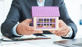 Businessman in suit holding house model. Loan or rent concept. Middle section of businessman holding home model. Loan concept royalty free stock image