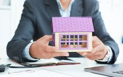 Businessman in suit holding house model. Loan or rent concept. Middle section of businessman holding home model. Loan concept royalty free stock photos