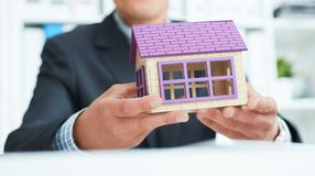 Businessman in suit holding house model. Loan or rent concept. Middle section of businessman holding home model. Loan concept stock photography