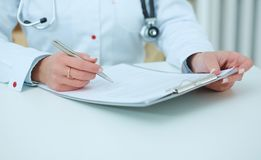 Middle section of female doctor holding application form and making notes while consulting patient. Stock Photos