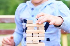 Middle section of the kid playing wood blocks tower game for practicing physical and mental skill. royalty free stock photography