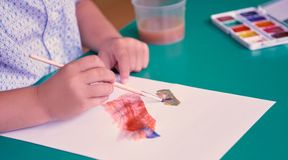Middle section of little child drawing with colorful watercolors indoor. Concept of aesthetic education in the. Middle section of little child drawing with royalty free stock images