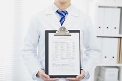 Middle section of male medical doctor showing blank medical chart on clipboard. Male european doctor with lab coat in his office holding a clipboard with Royalty Free Stock Image