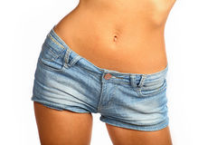 Middle section of a young and fit woman with short denim pants Royalty Free Stock Images