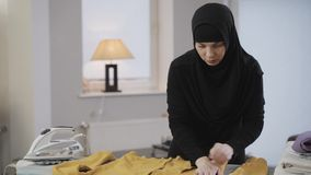 Middle shot of beautiful muslim woman in traditional clothes ironing yellow pullover. Diligent young housewife in hijab