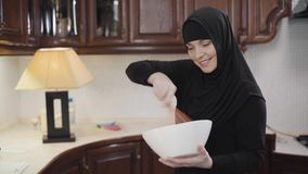 Middle shot of beautiful muslim woman in traditional hijab looking at camera and whisking. Modern eastern lady cooking