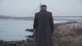 Middle shot of lonely Caucasian man walking along rocky riverbank and thinking. Back view of young guy in elegant coat