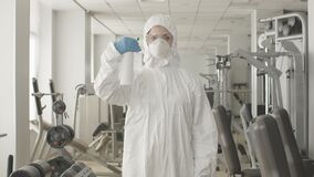 Middle shot of serious woman in protective suit and respirator spraying disinfectant in gym. Portrait of concentrated
