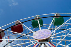 Middle and upper part of ferris wheel with red and green bowls against blue sky with thin clouds. Stock Image