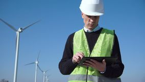 Engineer using digital tablet against wind turbine. Middle view of engineer working with digital tablet against wind turbine on sunny day stock footage