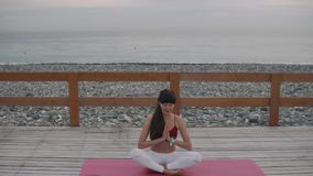 Woman meditates in nature. Middle-woman is meditating on outdoor terrace on sea beach. Sporty woman practices yoga outside, fresh sea air helps concentrating stock video