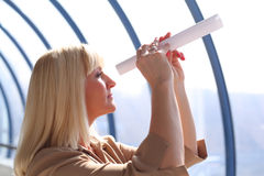 Middleaged businesswoman looks in  paper tube Royalty Free Stock Image