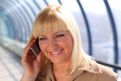 Middleaged businesswoman talks on cellular phone Royalty Free Stock Image
