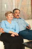 Middleaged couple watching tv home. Middle aged couple watching tv home and sitting on couch Royalty Free Stock Image