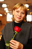Middleaged woman with rose in hands Royalty Free Stock Images