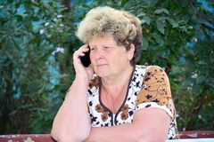 Middleaged woman talks on  mobile phone Royalty Free Stock Image