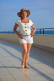 Middleagede woman on balcony over sea full body Royalty Free Stock Image