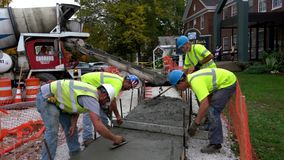 Middlebury,佛蒙特- 20181010 -建筑队使在最近倾吐的水泥边路的混凝土光滑 影视素材
