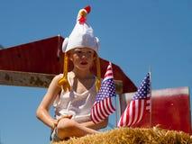 MIDDLETON, IDAHO - 4 JUILLET : Enfant non identifié s'asseyant sur un certain foin avec quelques drapeaux américains pendant le 4è Images libres de droits