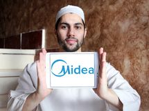 Midea Group logo. Logo of Midea Group on samsung tablet holded by arab muslim man. Midea Group is a Chinese electrical appliance manufacturer, headquartered in stock images