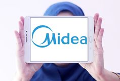 Midea Group logo. Logo of Midea Group on samsung tablet holded by arab muslim woman. Midea Group is a Chinese electrical appliance manufacturer, headquartered in stock photos