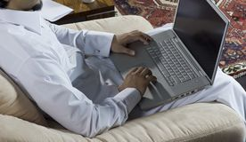 Mideastern man using laptop at home, with a cup of cofee and doc Royalty Free Stock Photos