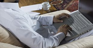 Mideastern man using laptop at home, with a cup of cofee and doc Royalty Free Stock Photo