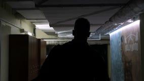 Mideo del movimento lento dell'uomo che va alla palestra nel corridoio scuro archivi video