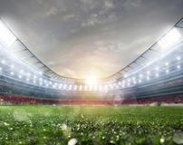 Midfield of grass soccer stadium field with headlights. Midfield of grass soccer stadium field during sundown with headlights stock photo