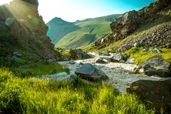 Midi au pied de la montagne avec le ciel bleu et du courant des montagnes rocailleux parmi des pierres photo stock