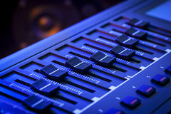 MIDI Faders on a Controller Keyboard. Close-up of a row of faders on a MIDI controller Keyboard with a speaker out of focus in the background Royalty Free Stock Photos